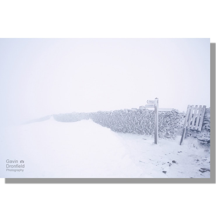 white-out at pen-y-ghent summit with dry stone wall and fingerpost under deep snow during blizzard