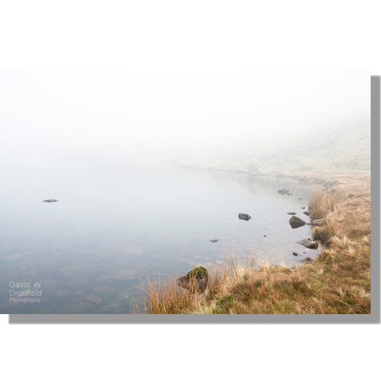 reflections in peaceful greendale tarn under middle fell shrouded by thick mist