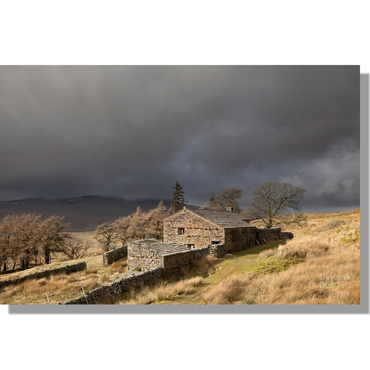 ruined farmstead high hall on high way track above mallerstang under dark brooding skies with wild boar fell in the background