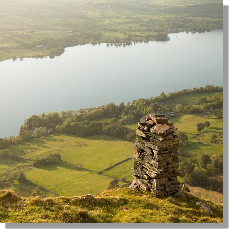 bonscale tower columnar cairn on bonscale fell overlooking ullswater amid surrounding green farm fields in summer