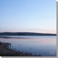 calm malham tarn from shore under serene clear blue sky at sunset