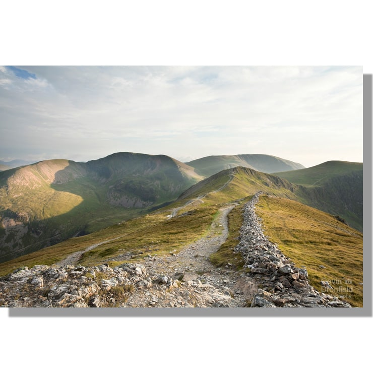 eel crag, grasmoor, sand hill from ruined dry stone wall on grisedale pike illuminated by low summer sun under grey sky