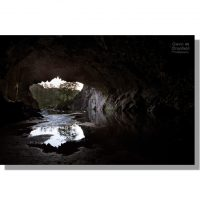 rydal cave quarry entrance reflected in a pool seen from inside the dark slate cavern