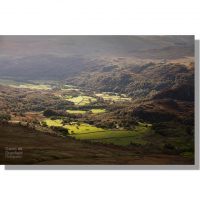 duddon valley sunlit green farm fields surrounded by dark brooding fells seen from dow crag