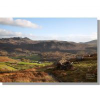 ruined peat houses atop boot bank overlooking autumnal eskdale valley under blue skies with green crag in background