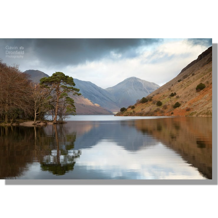 great gable and wastwater screes reflected in wast water from source of river irt under cloudy skies
