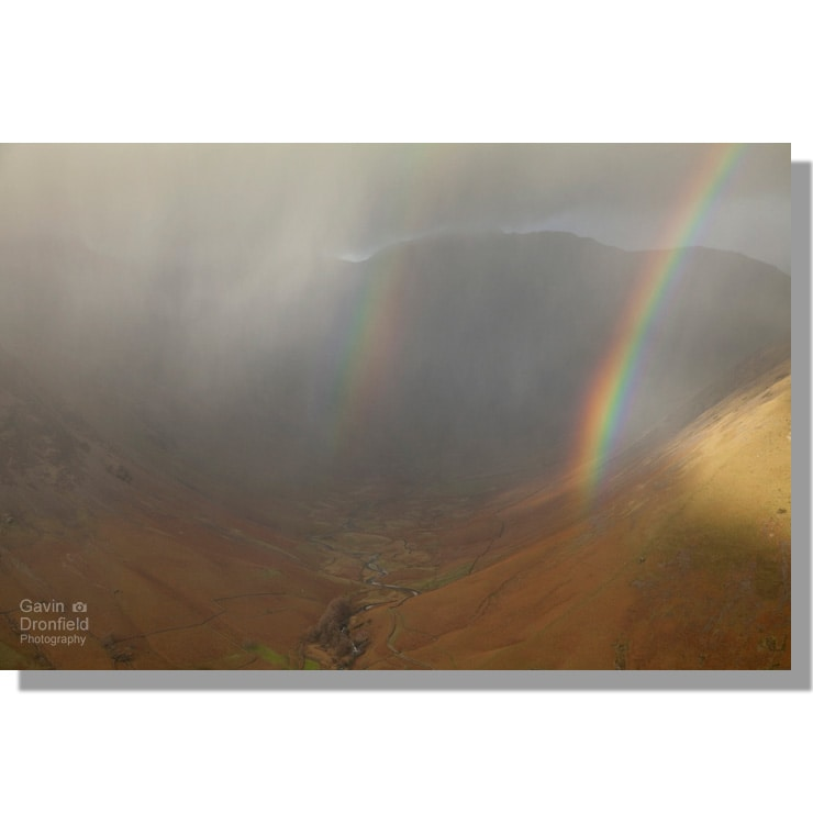 double rainbow in dark hailstorm clouds above mosedale valley near wasdale head seen from lingmell