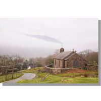 st. James church next to country lane above buttermere village on a grey autumnal morning amidst mist enshrouded fells