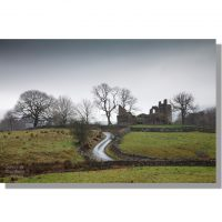 ruined keep of pendragon castle on a grassy hill surrounded by bare trees in winter under darn leaden skies next to a dry stone walled country lane