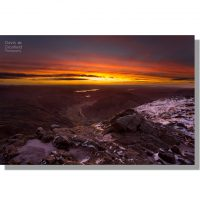 dramatic colourful dawn skies over windermere from ice-covered summit of harrison stickle above great langdale valley