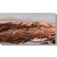 snow capped crinkle crags, bow fell and pike of stickle reddened by rising winter sun seen from harrison stickle
