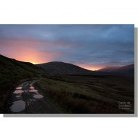 looking along the old coach road track towards clough head under colourful sunset sky