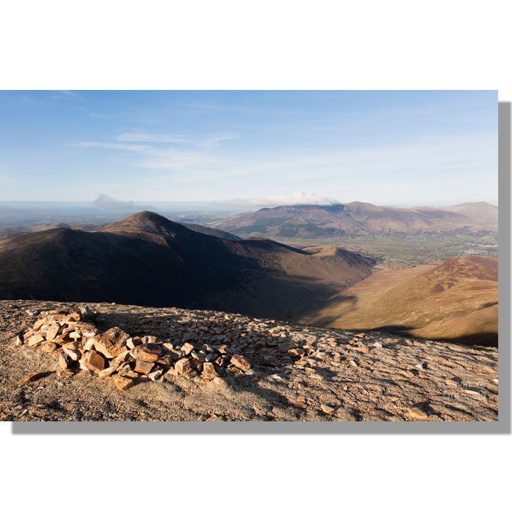 view from crag hill summit stone shelter of coledale in the shadow of grisedale pike and a distant skiddaw under blue skies
