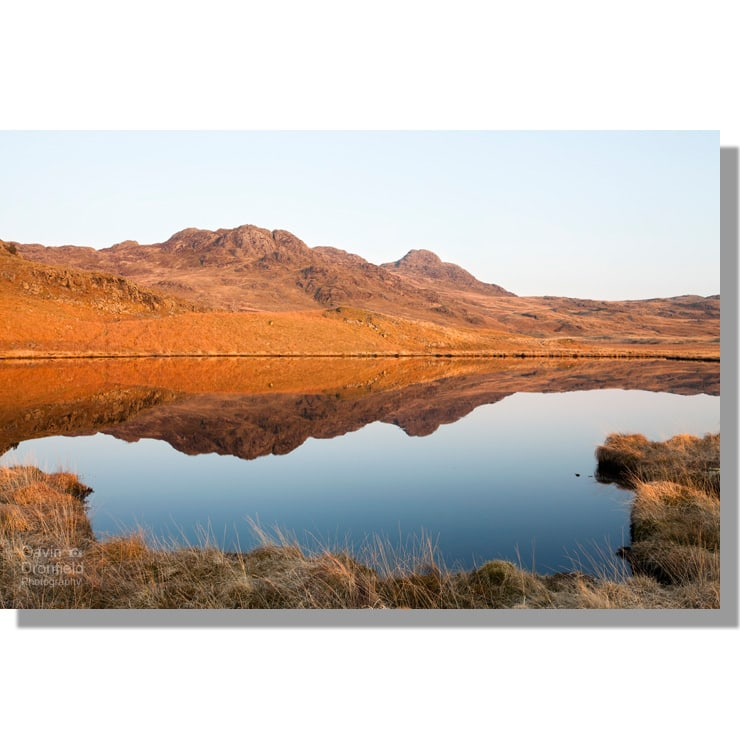 green crag and crook crag reflected in calm low birker tarn bathed in red light at sunset under clear blue skies