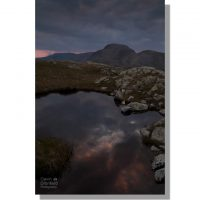 lingcomb tarns reflecting dark red sunset clouds with green gable and great gable on the skyline