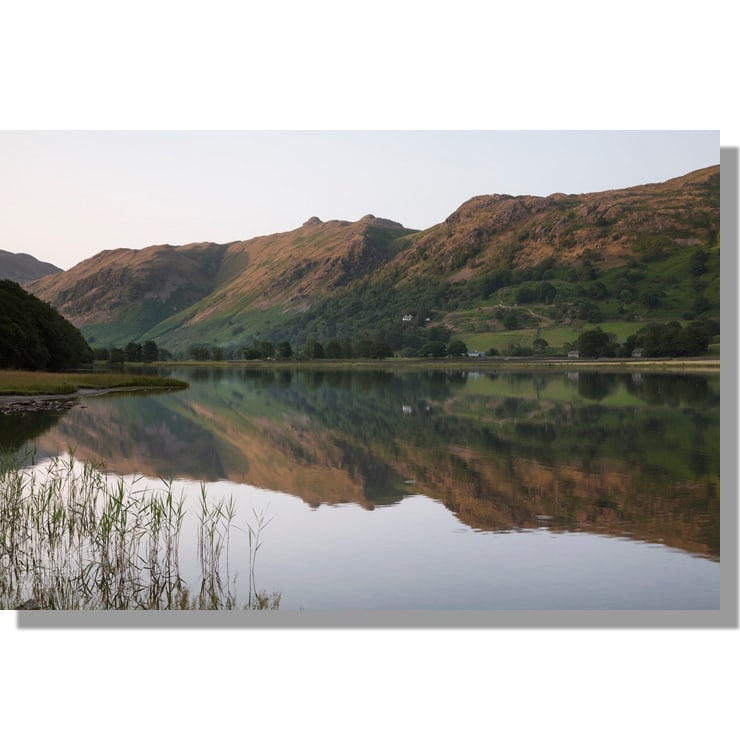 reflections in brothers water of angletarn pikes summit basking in red sunset light under blue sky