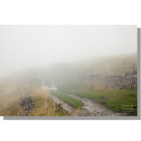 west cam road walled track and old packhorse route running over dodd fell hill on a misty drizzly day
