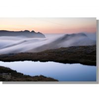silhouetted langdale pikes above cloud enveloped rossett pike from calm tarn on tongue head under red dawn skies