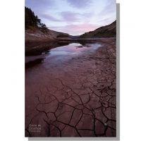 cracked red mud revealed by retreating haweswater water levels during dry period under red dawn skies